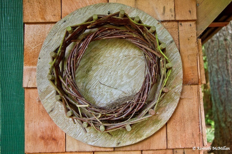 Wreath Maker - A jig I made for my wife for making a woven wreath.  The twigs woven beteen the pegs are hazelnut.  The smaller twisted wreath is probably cotoneaster.
